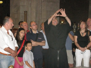 Padre Giustino Casciano mentre spiega l'Arca di Sant'Agostino ai pellegrini