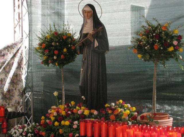 I fedeli offrono fiori e ceri alla statua di santa Rita nel chiostro del Convento di San Pietro in Ciel d'Oro