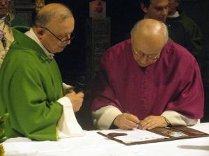 Monsignor Giuseppe Torchio mentre firma per il rinnovo del Comitato Pavia Città di Sant'Agostino